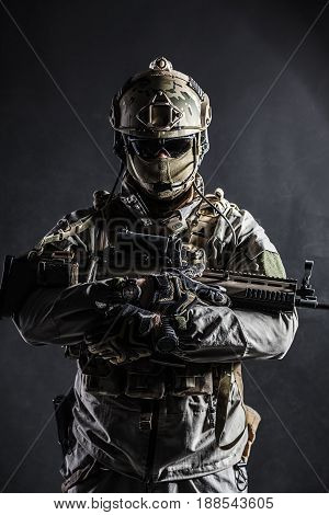 Army soldier in Protective Combat Uniform holding Special Operations Forces Combat Assault Rifle. Studio shot, dark contrast, cropped, black dark background