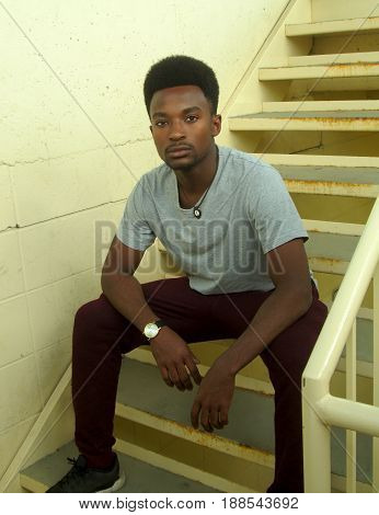 young man sitting in the stair concrete walls