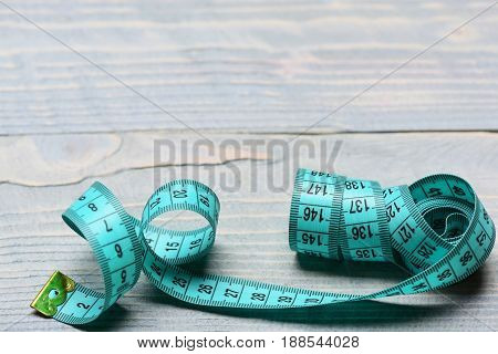 Tape For Measuring In Cyan Color On Vintage Wooden Background