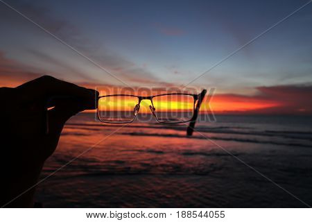 Sunset and ocean through glasses in a hand