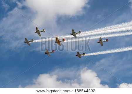 EDEN PRAIRIE MN - JULY 16 2016: AT6 Texan planes fly overhead against cloudy sky with smoke trails at air show. The AT6 Texan was primarily used as trainer aircraft during and after World War II.