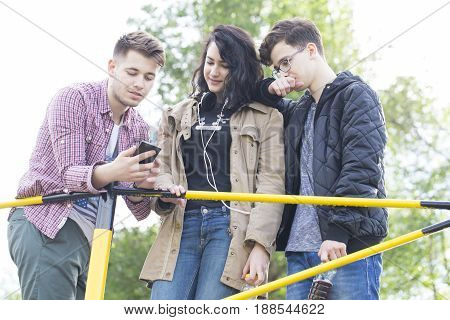 Three smiling young people two boys and a girl talking and looking at the mobile phone. They are having a good timene. Lens flare. Selective focus and smal depth of field