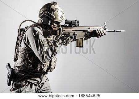 Army soldier in Protective Combat Uniform holding Special Operations Forces Combat Assault Rifle. Shooting weapon close up. Studio shot, isolated on white background