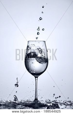Water bubbles falling and clean water splash out of wineglass standing on the glass with splashing water against light background. Transparent and pure water. Care for the environment and health. Concept of the healthy lifestyle.