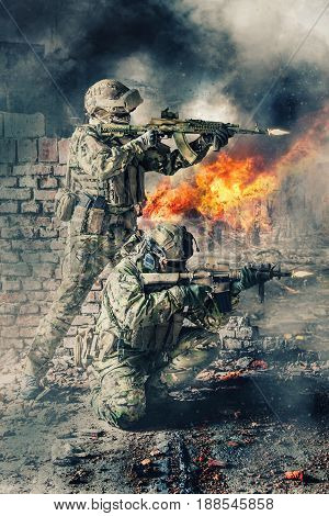 Pair of special forces shooting a weapons. Brothers in arms in action. Guns blazing, ruined walls of buildings, explosions, gunfire and smoke on background
