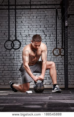 Young sportsman holding kettlebell with his arms on the cross fit gym floor against brick wall. Athlete man in the grey sporty shorts and sportive shoes. Energy and power. Healthy lifestyle.