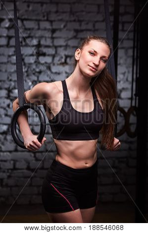 Portrait of a young sporty woman in the black sportwear training arms with gymnastics rings in the cross fit gym against brick wall. Woman in the t-shirt and shorts. Healthy lifestyle. Portrait of the sporty woman. Vertical photo.