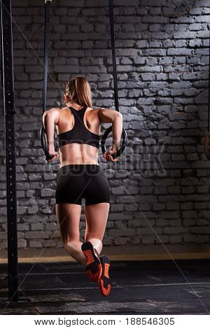 Rear view photo of beautiful young sporty woman in the black sportwear doing pull-ups exercise using gymnastic rings against brick wall at gym. Woman in the t-shirt, shorts and sportive shoes. Healthy lifestyle.