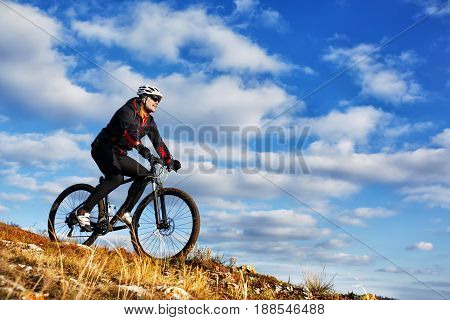 Cyclist on the Beautiful Meadow Trail on sunny day. Spring season. Cyclist in the helmet. Beautiful landscape, blue sky with white clouds and mound. Downhill.