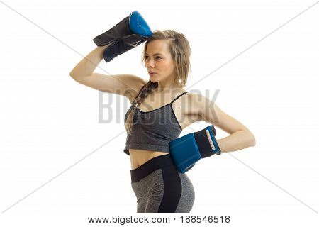 Attractive blonde lady in sports uniform and boxing gloves posing in studio on white background