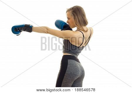 Young blonde girl practicing boxing in blue gloves isolated on white background