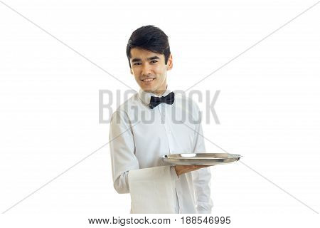Cheerful brunette waiter man with silver tray in hands smiling isolated on white background