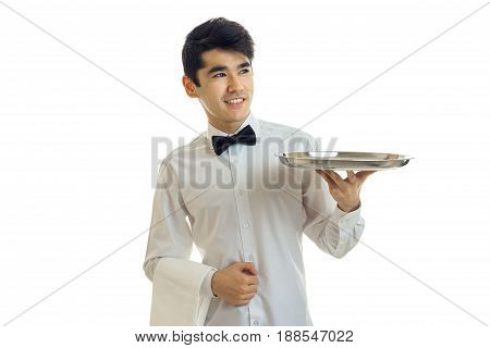 young cheerful brunette waiter man in uniform and tray in hands smiling and looking aside isolated on white background