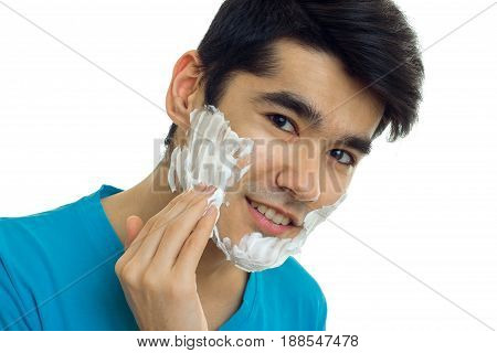 handsome man with shaving cream on face smiling and looking at the camera isolated on white background