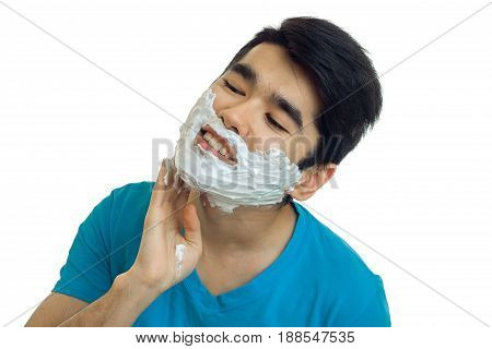 Cute young man in blue t-shirt with shaving cream on his face smiling isolated on white background