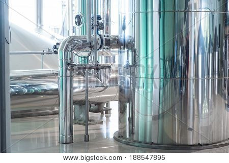 Modern beer plant brewery , with brewing kettles, vessels, tubs and pipes made of stainless steel.