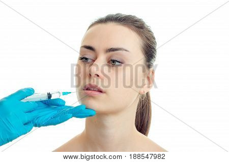 Portrait of a young girl at a cosmetologist who gloved makes her prick on the lips isolated on white background