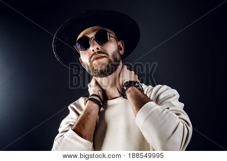 From below handsome stylish man in sunglasses and hat touching his neck. Horizontal studio shot.