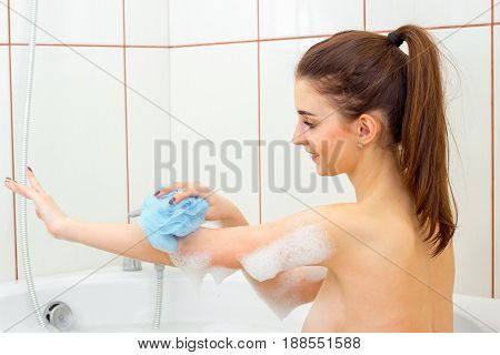 young hot girl bathes in the bathtub and rubs the body sponge closeup