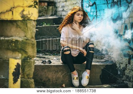 Beautiful Vape Teenager. Portrait Of A Pretty Young White Girl With Red Curly Hair Vaping An Electro