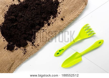 rake, trowel, ground and sack for gardening on white desk background top view