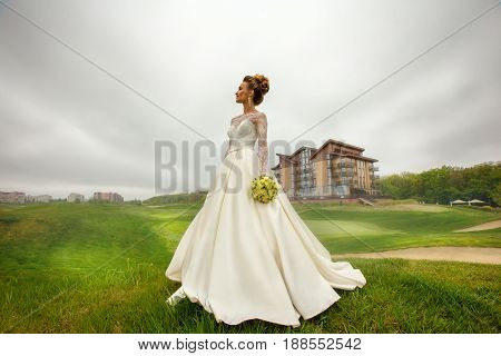 Gorgeoun young bride in wedding dress outdoors at raining weather