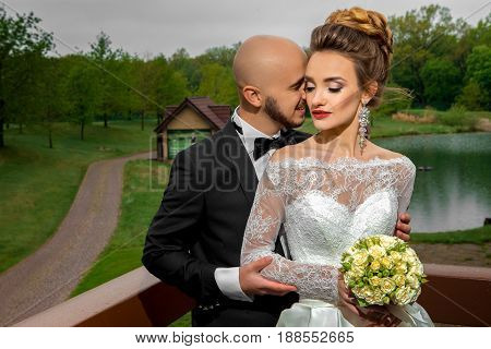 Happy young family in wedding suits hugging outdoors