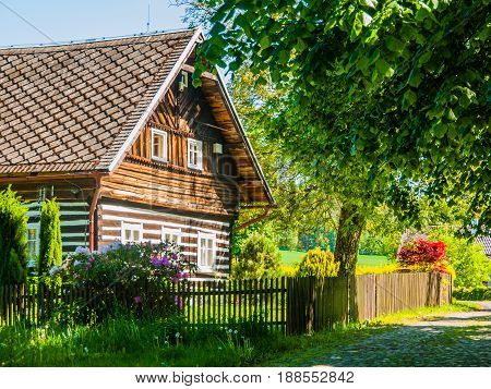 Old traditional timbered cottage with romantic and idyllic lush green flower garden with wooden fence on sunny summer day. Czech rural architecture.