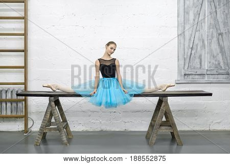 Beautiful ballerina sits on the split on the long wooden table on the textured white wall background in the studio. She wears a black leotard with a cyan tutu and pointe shoes. Horizontal.