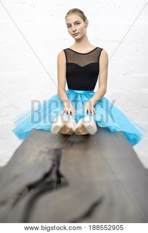 Attractive ballerina sits on the wooden table on the textured white wall background in the studio. She wears a black leotard with a cyan tutu and pointe shoes. She looks into the camera. Vertical.
