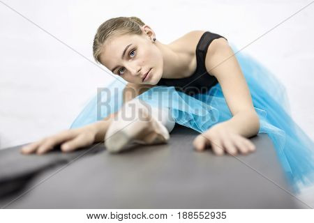 Charming ballerina presses her torso to the leg on the wooden table on the white wall background in the studio. She wears a black leotard with cyan tutu and pointe shoes. Girl looks into the camera.