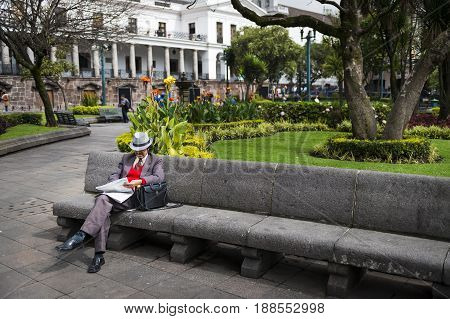 Quito Ecuador - January 29 2014: Man reading a newspaper in a bench in a park in the Independence Square at the city of Quito in Ecuador