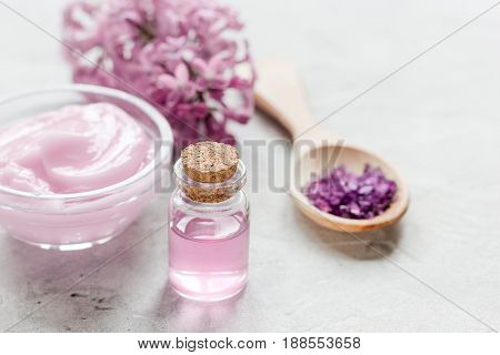 spa cosmetic set with lilac flowers on stone desk background