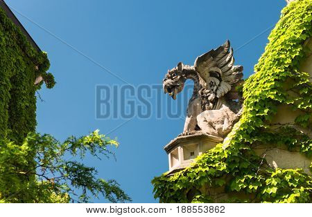 Big Stone Gargoyle On A Gate In A Park