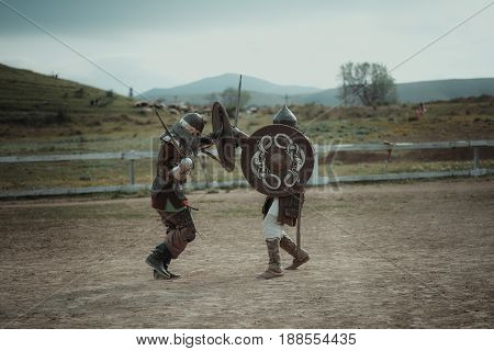 Russia Feodosiya May 9 2017: Medieval joust knights in helmets and chain mail battle on swords with shields in their hands reconstruction. European Middle Ages Performance festival