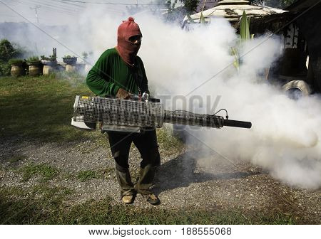 Man work fogging to eliminate mosquito for preventing spread dengue fever in Thailand.