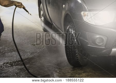 Washing black car by high pressure water. Car wash closeup.