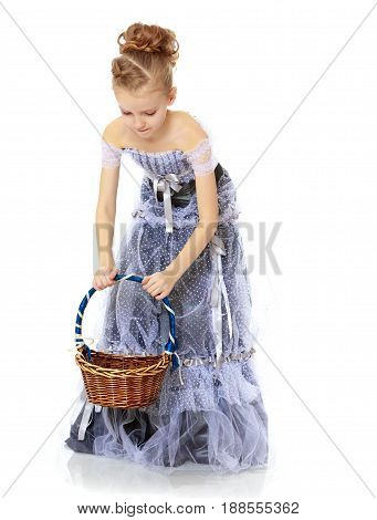 Adorable little blond girl dressed in long Princess dress.A girl holds a wicker basket.Isolated on white background.