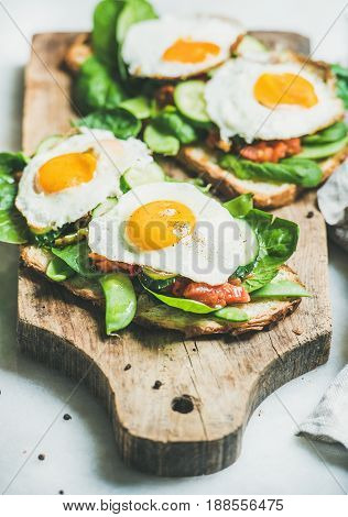 Healthy breakfast sandwiches. Bread toasts with fried eggs and fresh vegetables on rustic wooden board over grey marble background, selective focus. Clean eating, healthy, diet, detox food concept