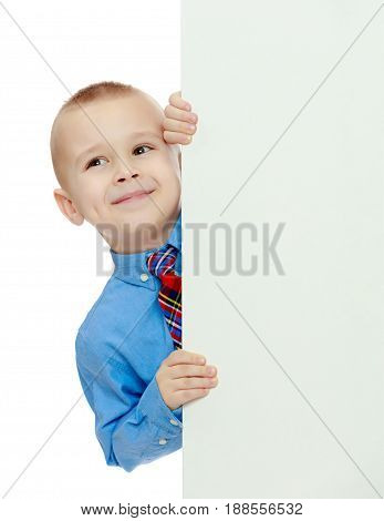 Beautiful little boy in a blue shirt and tie peeking from behind the banner.Isolated on white background.
