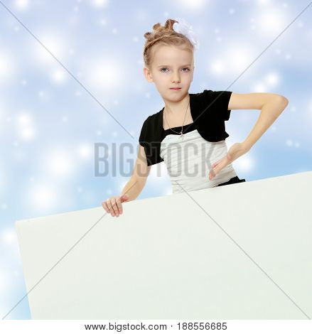 Beautiful little blonde girl dressed in a white short dress with black sleeves and a black belt.The girl peeks out from behind white advertising banner and shows a finger at him.