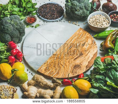 Clean eating healthy cooking ingredients. Vegetables, beans, grains, greens, fruit, spices over grey background, empty marble and wooden board in center with copy space, selective focus
