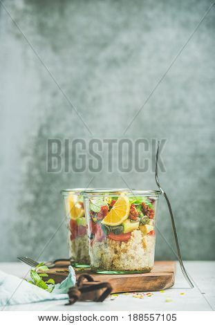 Healthy salad with quionoa, avocado, dried tomatoes, basil, mint, orange in glass jars on wooden board, grey wall at background, selective focus, copy space. Clean eating, vegan, detox food concept