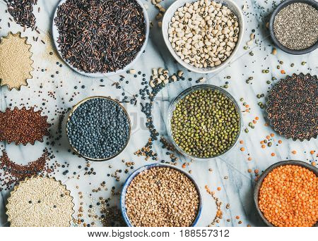 Various raw uncooked grains, beans, cereals in bowls and cups for healthy cooking over grey marble background, top view. Clean eating, dieting, healthy, detox, vegan, vegetarian food concept