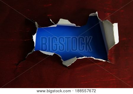hole torn in a piece of paper with blue interior
