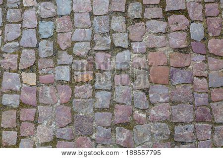Stone granite cobblestoned pavement background or texture. Abstract background of old cobblestone pavement close-up in Prague.