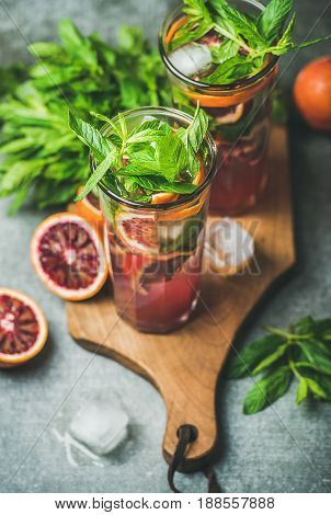 Blood orange citrus lemonade with fresh mint and ice cubes in tall glasses on wooden board over dark brown stone background. Refreshing summer drink concept