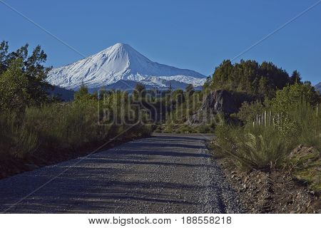 Snow capped peak of Antuco Volcano (2,979 metres) rising above a gravel road in Laguna de Laja National Park in the Bio Bio region of Chile.