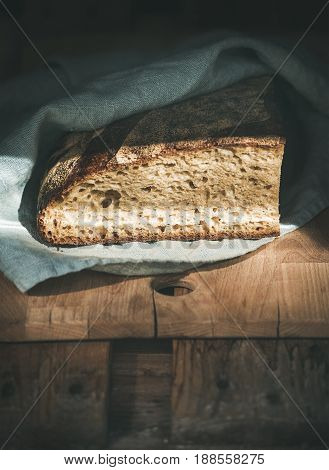 Rustic French rye bread loaf covered with kitchen towel over shabby wooden board, selective focus, vertical composition, copy space