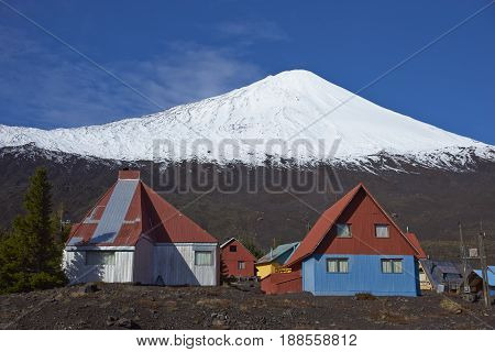 Snow capped peak of Antuco Volcano (2,979 metres) rising above the small ski resort in Laguna de Laja National Park in the Bio Bio region of Chile.